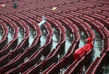 CINCINNATI - MARCH 31:  Fans sit through a steady rain before the game between the Cincinnati Reds and the Arizona Diamondbacks on March 31, 2008 at Great American Ball Park in Cincinnati, Ohio.  (Photo by Andy Lyons/Getty Images)