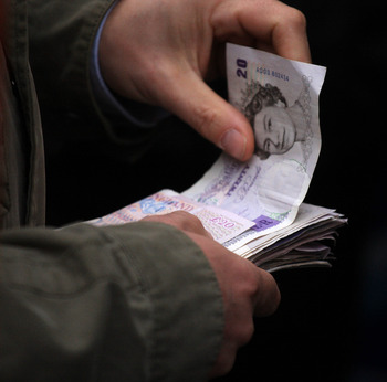 CHELTENHAM, ENGLAND - MARCH 14:  A punter hands over money for a bet at Cheltenham Racecourse on March 14, 2008, in Cheltenham, England. Today was the fourth day of The Annual National Hunt Festival held at the Gloucestershire track.  (Photo by Julian Her