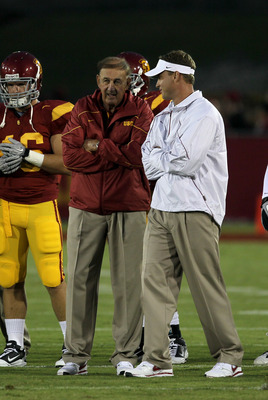 LOS ANGELES, CA - SEPTEMBER 11:  Head coach Lane Kiffin (R) and his father and defensive coordinator Monte Kiffin of the USC Trojans  talk during warmups for their game with the Virginia Cavaliers at Los Angeles Memorial Coliseum on September 11, 2010 in