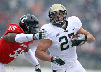 CINCINNATI, OH - DECEMBER 04:  Henry Hynoski #27 of the Pittsburgh Panthers runs with the ball while defended by Brandon Mills #58 of the Cincinnati Bearcats during the Big East Conference game against at Nippert Stadium on December 4, 2010 in Cincinnati,