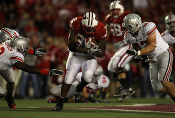 MADISON, WI - OCTOBER 16: John Clay #32 of the Wisconsin Badgers runs between Orhian Johnson #19 and Nathan Williams #43 of the Ohio State Buckeyes at Camp Randall Stadium on October 16, 2010 in Madison, Wisconsin. Wisconsin defeated Ohio State 31-18. (Ph