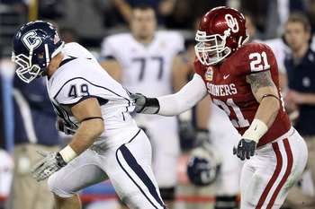 GLENDALE, AZ - JANUARY 01:  Anthony Sherman #49 of the Connecticut Huskies runs the ball as his jersey is grabbed by Tom Wort #21 of the Oklahoma Sooners in the fourth quarter during the Tostitos Fiesta Bowl at the Universtity of Phoenix Stadium on Januar