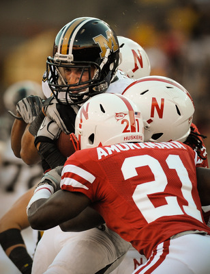 LINCOLN, NE - OCTOBER 30: Tight end Michael Egnew #82 of the Missouri Tigers takes a hit from cornerback Prince Amukamara #21 and teammates of the Nebraska Cornhuskers during second half action of their game at Memorial Stadium on October 30, 2010 in Linc