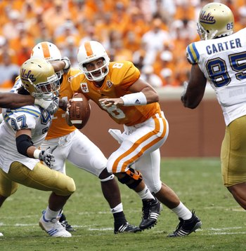 KNOXVILLE, TN - SEPTEMBER 12: Jonathan Crompton #8 of the Tennessee Volunteers scrambles against David Carter #85 of the UCLA Bruins on September 12, 2009 at Neyland Stadium in Knoxville, Tennessee. UCLA beat Tennessee 19-15. (Photo by Joe Murphy/Getty Im