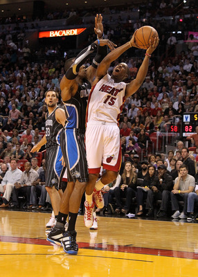 MIAMI, FL - MARCH 03:  Mario Chalmers #15 of the Miami Heat is fouled by Dwight Howard #12 of the Orlando Magic during a game at American Airlines Arena on March 3, 2011 in Miami, Florida. NOTE TO USER: User expressly acknowledges and agrees that, by down