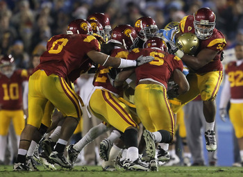 PASADENA, CA - DECEMBER 04:  Chris Galippo (R) #54 of the USC Trojans tackles Malcolm Jones #28 of the UCLA Bruins during the second half at the Rose Bowl on December 4, 2010 in Pasadena, California. USC defeated UCLA 28-14.  (Photo by Jeff Gross/Getty Im