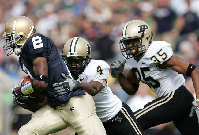 SOUTH BEND, IN - SEPTEMBER 30:  Darrin Walls #2 of the Notre Dame Fighting Irish runs with the ball against Fabian Martin #4 and David Pender #35 of the Purdue Boilermakers September 30, 2006 at Notre Dame Stadium in South Bend, Indiana. Notre Dame won 35