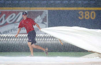ATLANTA - MAY 28:  A member of the grounds crew pulls the tarp over the infield after a delay in play was called due to rain during the game between the Atlanta Braves and the Pittsburgh Pirates at Turner Field on May 28, 2010 in Atlanta, Georgia.  (Photo