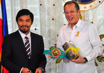 MANILA, PHILIPPINES - NOVEMBER 20:  Boxer and congressman, Manny Pacquiao gives President Benigno Aquino III a shirt and memorabilia following his win of the WBC super welterweight crown against Mexican Antonio Margarito on November 20, 2010 in Manila, Ph