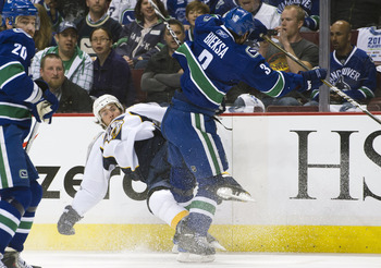 VANCOUVER, CANADA - APRIL 28: Kevin Bieksa #3 of the Vancouver Canucks knocks Mike Fisher #12 of the Nashville Predators down onto the ice during the first period in Game One of the Western Conference Semifinals during the 2011 NHL Stanley Cup Playoffs on