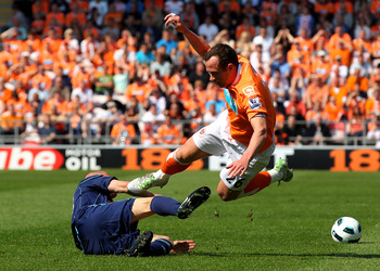 BLACKPOOL, ENGLAND - APRIL 30:   Andy Wilkinson of Stoke City challenges Charlie Adam of Blackpool during the Barclays Premier League match between Blackpool and Stoke City at Bloomfield Road on April 30, 2011 in Blackpool, England. (Photo by Clive Brunsk
