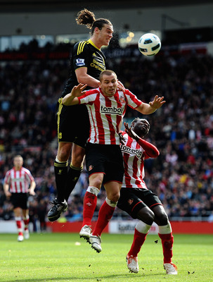 SUNDERLAND, ENGLAND - MARCH 20: Andy Carroll of Liverpool battles with Phil Bardsley and John Mensah of Sunderland during the Barclays Premier League match between Sunderland and Liverpool at the Stadium of Light on March 20, 2011 in Sunderland, England.