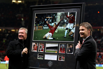 MANCHESTER, ENGLAND - DECEMBER 13:  Manchester United Manager Sir Alex Ferguson presents Ole Gunnar Solskjaer with a print of his winning goal celebration from the 1999 Champions League Final prior to the Barclays Premier League match between Manchester U