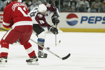 DENVER - MAY 25: Chris Drury #18 of the Colorado Avalanche dumps the puck against the Detroit Red Wings in the second period of game four of the Western Conference Finals during the NHL Stanley Cup Playoffs at the Pepsi Center in Denver, Colorado, on May