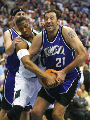 MINNEAPOLIS - MAY 14:  Vlade Divac #21 of  the Sacramento Kings is fouled by Ervin Johnson #40 of the Minnesota Timberwolves in Game five of the Western Conference Semifinals of the 2004 NBA Playoffs on May 14, 2004 at the Target Center  in Minneapolis, M