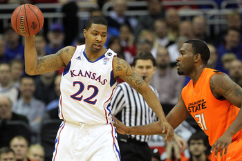 KANSAS CITY, MO - MARCH 10:  Marcus Morris #22 of the Kansas Jayhawks looks to move the ball against Matt Pilgrim #31 of the Oklahoma State Cowboys during their quarterfinal game in the 2011 Phillips 66 Big 12 Men's Basketball Tournament at Sprint Center