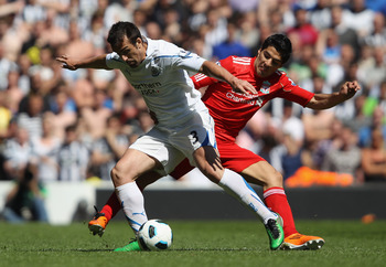 LIVERPOOL, ENGLAND - MAY 01: Jose Enrique of Newcastle United holds off  Luis Suarez of Liverpool during the Barclays Premier League match between Liverpool  and Newcastle United at Anfield on May 1, 2011 in Liverpool, England.  (Photo by Clive Brunskill/