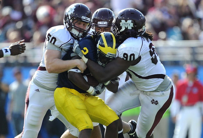 JACKSONVILLE, FL - JANUARY 01:  Chris White #50 and Pernell McPhee #90 of the Mississippi State Bulldogs tackle Vincent Smith # 2 of the Michigan Wolverines during the Gator Bowl at EverBank Field on January 1, 2011 in Jacksonville, Florida  (Photo by Ric
