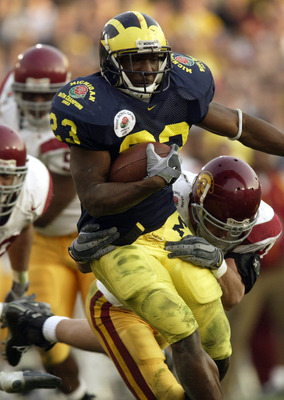 PASADENA, CA - JANUARY 1:  Running back Chris Perry #23 of the Michigan Wolverines attempts to break loose from the grasp of a USC Trojans defender during the 2004 Rose Bowl game on January 1, 2004 at the Rose Bowl in Pasadena, California. USC defeated Mi