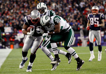 FOXBORO, MA - JANUARY 16:  Alge Crumpler #82 of the New England Patriots tries to avoid the tackle of Brodney Pool #22 of the New York Jets during their 2011 AFC divisional playoff game at Gillette Stadium on January 16, 2011 in Foxboro, Massachusetts.  (