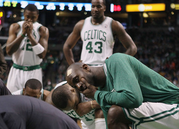 BOSTON, MA - FEBRUARY 06: Kevin Garnett #5,Glen Davis #11,Kendrick Perkins #43 and Von Wafter #12 of the Boston Celtics watch as medical personnel tend to Marquis Daniels of the Celtics after Daniels collided with Gilbert Arenas of the Orlando Magic on Fe