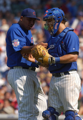 CHICAGO - JULY 2:  Carlos Zambrano #38 of the Chicago Cubs gets assistance from teammate Michael Barrett #5 after getting a cramp in his right forearm during a game against the Chicago White Sox on July 2, 2004 at Wrigley Field in Chicago, Illinois. The C