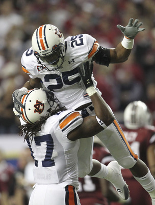 ATLANTA - DECEMBER 4:  Linebacker Daren Bates #25 of the Auburn Tigers is hoisted by teammate and linebacker Josh Bynes #17 after Bates' interception during the 2010 SEC Championship against the South Carolina Gamecocks at Georgia Dome on December 4, 2010