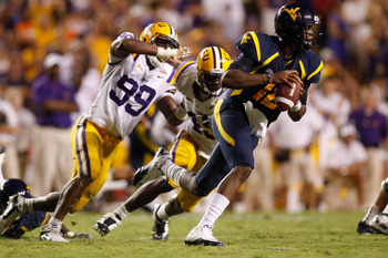 BATON ROUGE, LA - SEPTEMBER 25:  Quarterback Geno Smith #12 of the West Virginia Mountaineers avoids a tackle by Sam Montgomery #99 of the  Louisiana State University Tigers at Tiger Stadium on September 25, 2010 in Baton Rouge, Louisiana.  The Tigers def