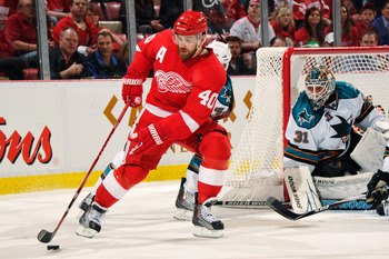 DETROIT - MAY 4:  Henrik Zetterberg #40 of the Detroit Red Wings controls the puck in front of goaltender Antti Niemi #31 of the San Jose Sharks in Game Three of the Western Conference Semifinals during the 2011 NHL Stanley Cup Playoffs on May 4, 2011 at