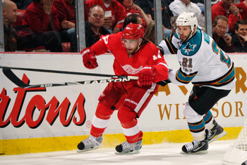 DETROIT - MAY 4:  Patrick Eaves #17 of the Detroit Red Wings and Scott Nichol #21 of the San Jose Sharks battle for position as they chase down a loose puck in the second period in Game Three of the Western Conference Semifinals during the 2011 NHL Stanle