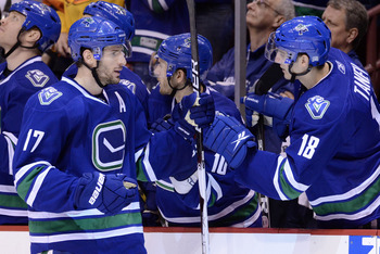 VANCOUVER, CANADA - JANUARY 22: Ryan Kesler #17 of the Vancouver Canucks is congratulated by teammate Chris Tanev #18 after scoring against the Calgary Flames during the third period in NHL action on January 22, 2011 at Rogers Arena in Vancouver, BC, Cana