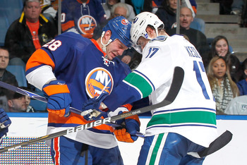 UNIONDALE, NY - JANUARY 11: Ryan Kesler #17 of the Vancouver Canucks butts heads with Zenon Konopka #28 of the New York Islanders during an NHL game at the Nassau Coliseum on January 11, 2011 in Uniondale, New York.  (Photo by Paul Bereswill/Getty Images)