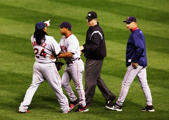 CLEVELAND - OCTOBER 18:  Manny Ramirez #24 of the Boston Red Sox is restrained by first base coach Luis Alicea #16 as he argues a call on a ball that he thought was a home run with right field umpire Paul Emmel #50 as Terry Francona #47 looks on in the th