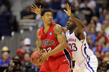 SAN ANTONIO, TX - MARCH 25:  Justin Harper #32 of the Richmond Spiders handles the ball against Mario Little #23 of the Kansas Jayhawks during the southwest regional of the 2011 NCAA men's basketball tournament at the Alamodome on March 25, 2011 in San An