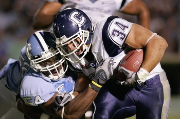 CHAPEL HILL, NC - OCTOBER 4:  Donald Brown #34 of the Connecticut Huskies carries the ball against Bruce Carter #54 of the North Carolina Tar Heels during the game at Kenan Stadium on October 4, 2008 in Chapel Hill, North Carolina.  (Photo by Kevin C. Cox