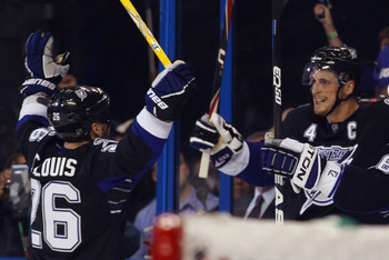TAMPA, FL - MAY 03: Martin St. Louis #26 of the Tampa Bay Lightning and Vincent Lecavalier #4 of the Tampa Bay Lightning celebrate a second period goal by Lecavalier against the Washington Capitals  in Game Three of the Eastern Conference Semifinals durin