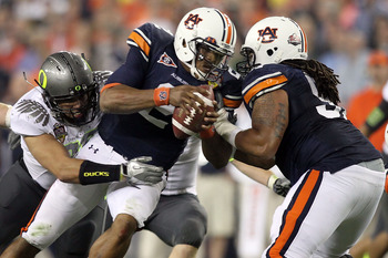GLENDALE, AZ - JANUARY 10:  Quarterback Cameron Newton #2 of the Auburn Tigers is sacked by Zac Clark #99 of the Oregon Ducks in the first quarter during the Tostitos BCS National Championship Game at University of Phoenix Stadium on January 10, 2011 in G