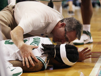 BOSTON, MA - FEBRUARY 06:  Marquis Daniels #8 the Boston Celtics is cared for after he collided with Gilbert Arenas #1 of the Orlando Magic on February 6, 2011 at the TD Garden in Boston, Massachusetts.  NOTE TO USER: User expressly acknowledges and agree