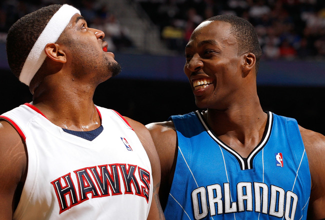ATLANTA - MAY 10:  Dwight Howard #12 of the Orlando Magic enjoys a laugh at a parody about him on the big screen next to Josh Smith #5 of the Atlanta Hawks during Game Four of the Eastern Conference Semifinals of the 2010 NBA Playoffs at Philips Arena on