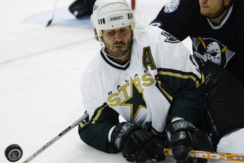DALLAS - MAY 3:  Mike Madano #9 of the Dallas Stars struggles for control of the puck with Ruslan Salei #24 of the Mighty Ducks of Anaheim in the 2003 Stanley Cup Western Conference semifinals at the American Airlines Center on May 3, 2003 in Dallas, Texa
