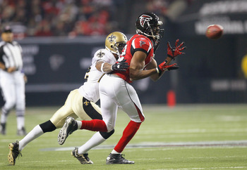 ATLANTA, GA - DECEMBER 27:  Michael Jenkins #12 of the Atlanta Falcons reaches for a pass in front of Tracy Porter #22 of the New Orleans Saints at Georgia Dome on December 27, 2010 in Atlanta, Georgia.  (Photo by Kevin C. Cox/Getty Images)