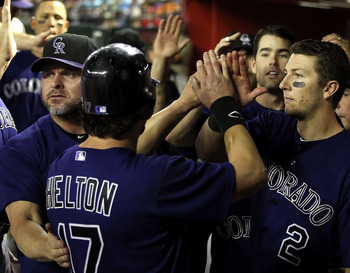 PHOENIX, AZ - MAY 05:  Todd Helton #17 of the Colorado Rockies high fives teammates Carney Lansford, Jason Giambi #23 and Troy Tulowitzki #2 after Helton scored a fourth inning run against the Arizona Diamondbacks during the Major League Baseball game at