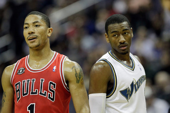 WASHINGTON, DC - FEBRUARY 28: John Wall #2 of the Washington Wizards (R) and Derrick Rose #1 of the Chicago Bulls (L) watch a foul shot at the Verizon Center in Washington on February 28, 2011 in Washington, DC. NOTE TO USER: User expressly acknowledges a