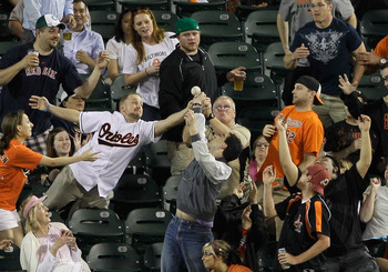 BALTIMORE, MD - APRIL 26:  Fans go after a ball thrown into the outfield after the third out of the sixth inning during the Boston Red Sox and Baltimore Orioles game at Oriole Park at Camden Yards on April 26, 2011 in Baltimore, Maryland.  (Photo by Rob C