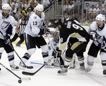 PITTSBURGH, PA - APRIL 27:  Dwayne Roloson #35 of the Tampa Bay Lightning makes a save on Pascal Dupuis #9 of the Pittsburgh Penguins in Game Seven of the Eastern Conference Quarterfinals during the 2011 NHL Stanley Cup Playoffs at Consol Energy Center on