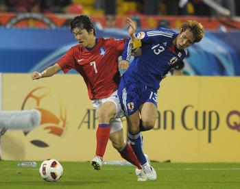 DOHA, QATAR - JANUARY 25: Hajime Hosogai of Japan and Ji-Sung Park of South Korea compete for the ball  during the AFC Asian Cup Semi Final match between Japan and South Korea at Al-Gharafa Stadium on January 25, 2011 in Doha, Qatar.  (Photo by Koki Nagah