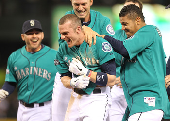 SEATTLE - MAY 06:  Brendan Ryan #26 of the Seattle Mariners is mobbed by teammates including starting pitcher Felix Hernandez #34 (R) after driving in the winning run in the ninth inning to defeat the Chicago White Sox 3-2 at Safeco Field on May 6, 2011 i