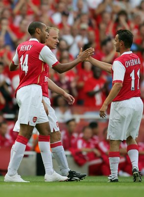 LONDON - JULY 22:  Thierry Henry (L) of Arsenal, is congratulated by teammates Dennis Bergkamp (C) and Marc Overmars (R), after scoring a goal during the Dennis Bergkamp testimonial match between Arsenal and Ajax at the Emirates Stadium on July 22, 2006 i
