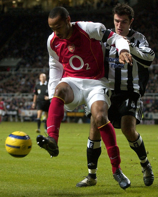 NEWCASTLE, ENGLAND - DECEMBER 29: Thierry Henry of Arsenal holds off Aaron Hughes of Newcastle during the FA Barclays Premiership match between Newcastle United and Arsenal at St.James Park on December 29, 2004 in Newcastle, England. (Photo by Matthew Lew