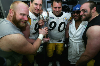 TAMPA, FL - FEBRUARY 01:  (L-R) Chris Hoke #76, Aaron Smith #91 Travis Kirschke #90,  Casey Hampton #98 and Brett Keisel #99 of the Pittsburgh Steelers celebrates with the Vince Lombardi trophy in the locker room after defeating the Arizona Cardinals duri